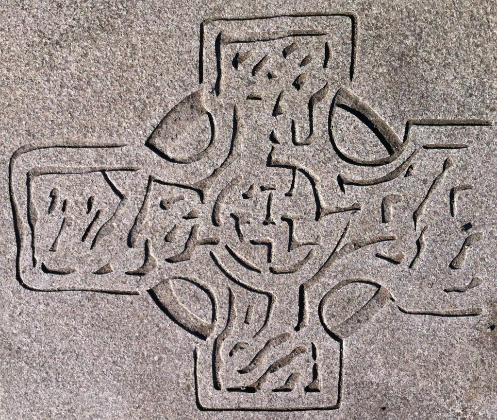 Photo of a stylised celtic cross carving in pavement.