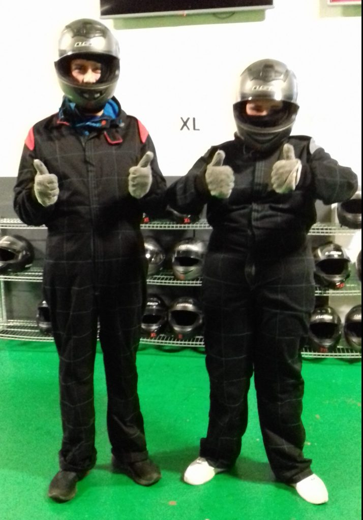 Photo of a youth worker and a young person dressed for go-karting with their thumbs up.