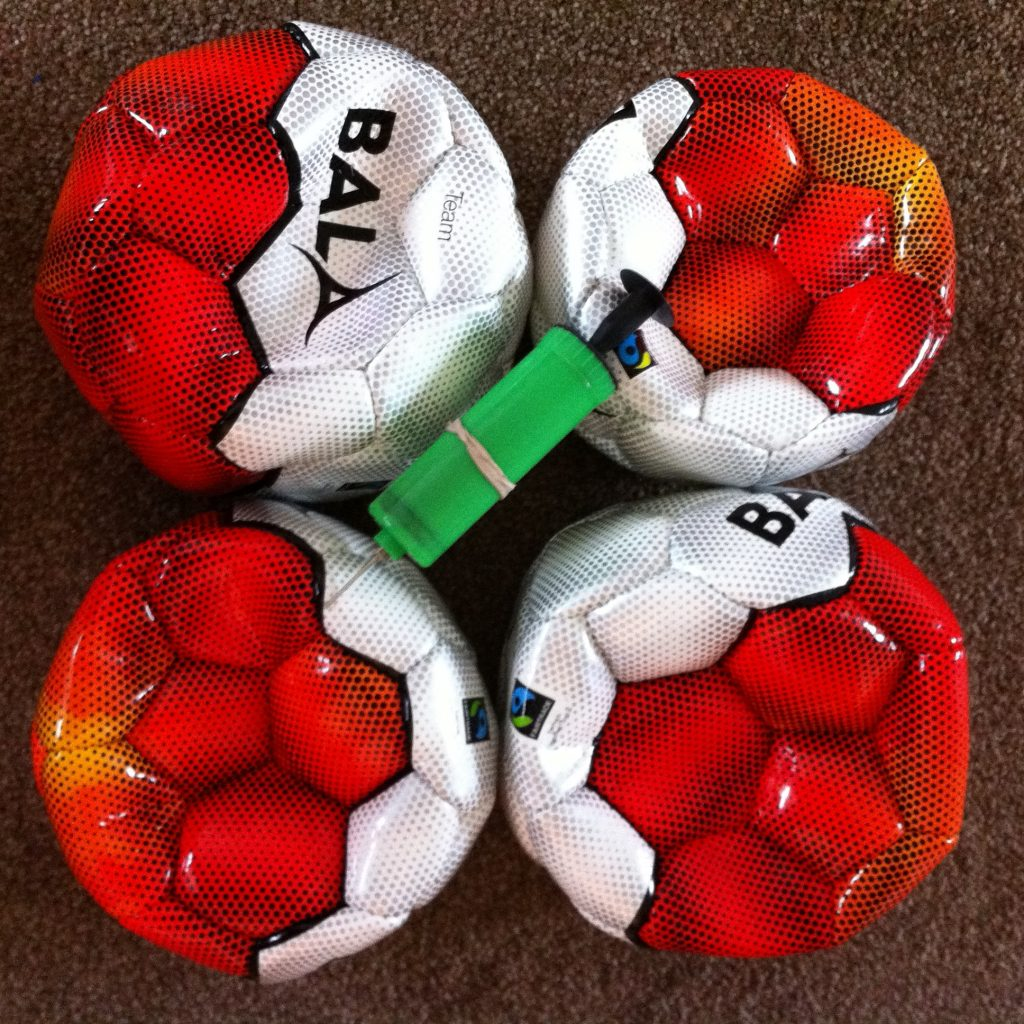 Photo of 3 footballs and a football pump