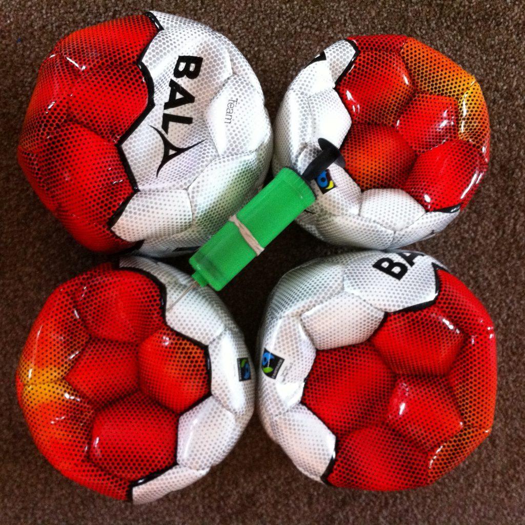 Photo of 3 footballs and a football pump