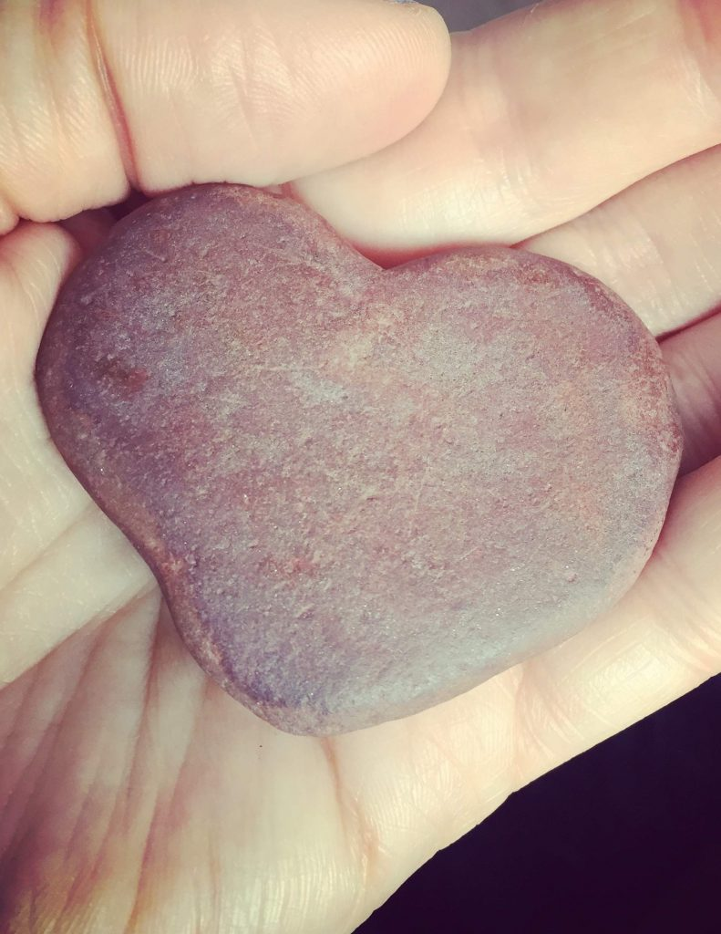 Hand holding a pink or red heart shaped stone.