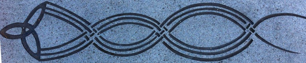 Celtic trinity symbol with tail  that streams behind it that intertwines to represent weaving (pavement carving in Govan).